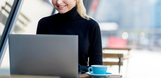 Vista frontal de uma mulher de negócios idosa trabalhando ao ar livre em um laptop
