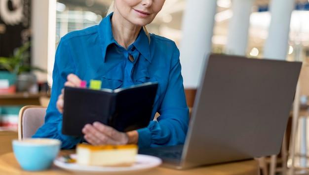 Vista frontal de uma mulher de negócios mais velha com óculos, escrevendo na agenda e olhando para o laptop