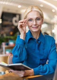 Vista frontal de uma mulher de negócios mais velha e inteligente com óculos segurando a agenda