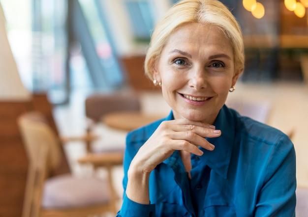 Vista frontal de uma mulher de negócios mais velha posando enquanto sai para trabalhar