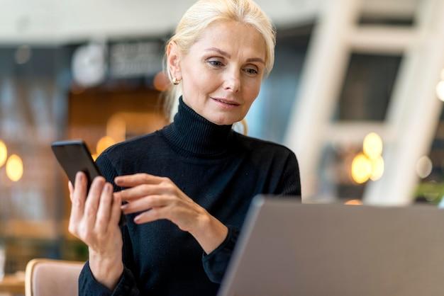 Vista frontal de uma mulher de negócios mais velha trabalhando em um laptop e smartphone