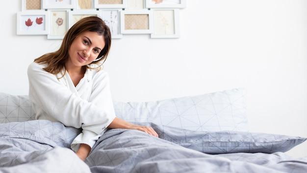 Vista frontal de uma mulher de pijama relaxando na cama