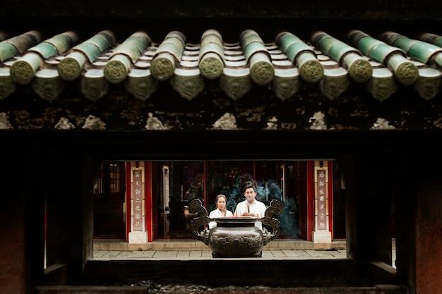 Vista frontal de uma mulher e um homem orando no templo com incenso queimando