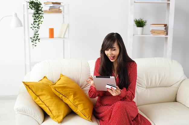 Vista frontal de uma mulher em casa pedindo itens à venda usando tablet e cartão de crédito