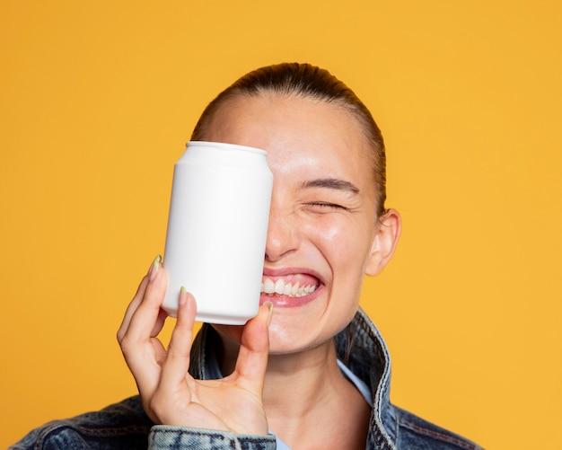 Vista frontal de uma mulher em êxtase com uma lata de refrigerante cobrindo o olho