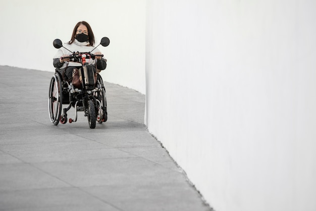 Vista frontal de uma mulher em uma cadeira de rodas com máscara e espaço de cópia
