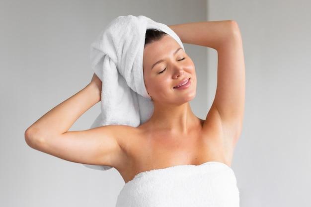 Vista frontal de uma mulher em uma toalha sendo fresca após os cuidados pessoais