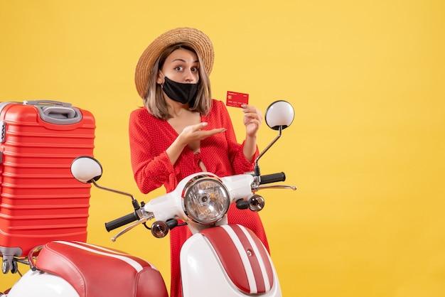 Vista frontal de uma mulher encantadora com máscara preta segurando um cartão de crédito perto de uma motocicleta