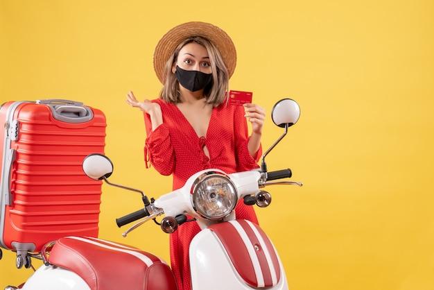 Vista frontal de uma mulher encantadora com máscara preta segurando um cartão de descontos perto de ciclomotor