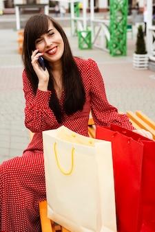 Vista frontal de uma mulher falando ao telefone sentada ao lado de sacolas de compras