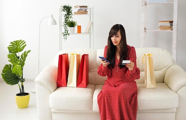 Vista frontal de uma mulher fazendo pedidos online em casa usando smartphone e cartão de crédito