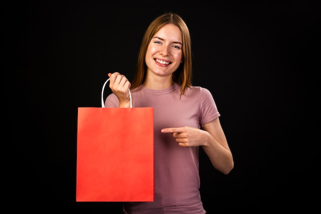 Vista frontal de uma mulher feliz, apontando para sua sacola vermelha