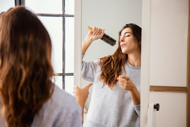 Vista frontal de uma mulher feliz cantando para a escova de cabelo em casa