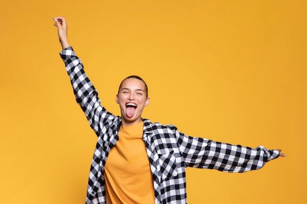 Vista frontal de uma mulher feliz com a língua de fora e camisa quadriculada