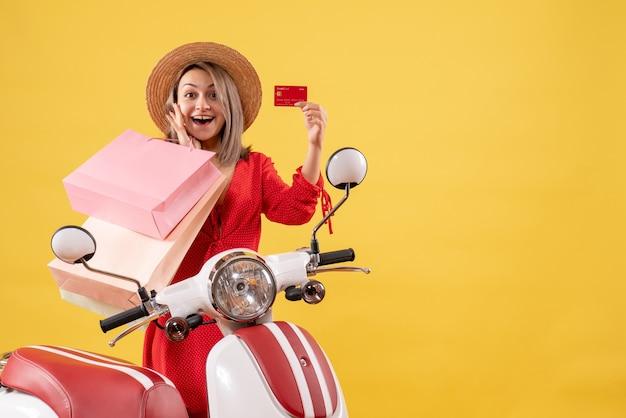 Vista frontal de uma mulher feliz com chapéu-panamá na motocicleta segurando sacolas de compras e um cartão