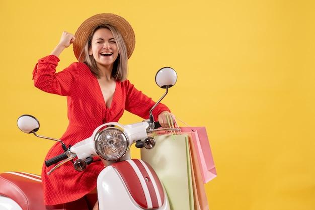 Vista frontal de uma mulher feliz com chapéu-panamá na motocicleta segurando sacolas de compras