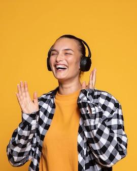 Vista frontal de uma mulher feliz com fones de ouvido