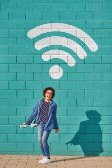 Vista frontal de uma mulher feliz em pé contra uma parede azul brilhante com um sinal de wi-fi acima de sua cabeça