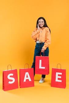 Vista frontal de uma mulher feliz posando com sacolas de compras à venda