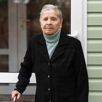 Vista frontal de uma mulher idosa com bengala em uma casa de repouso
