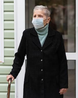 Vista frontal de uma mulher idosa com máscara médica e bengala