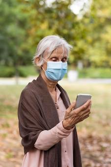 Vista frontal de uma mulher idosa com máscara médica segurando um smartphone