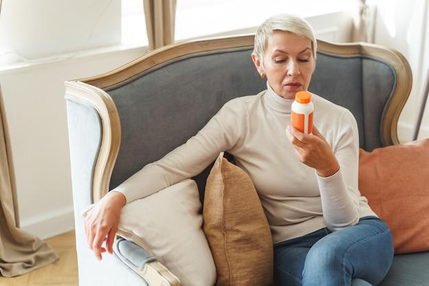 Vista frontal de uma mulher idosa descontente olhando para um recipiente de plástico em sua mão