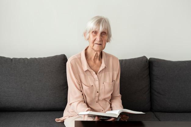Vista frontal de uma mulher idosa em uma casa de repouso lendo um livro