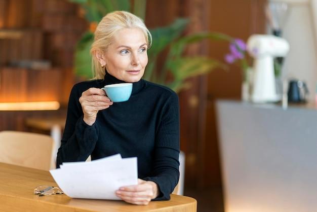 Vista frontal de uma mulher idosa no trabalho, tomando café e lendo jornais