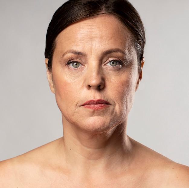 Vista frontal de uma mulher idosa posando estoica com maquiagem