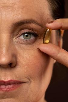 Vista frontal de uma mulher idosa segurando um comprimido de óleo