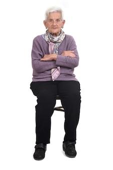 Vista frontal de uma mulher idosa sentada na cadeira com os braços cruzados no fundo branco