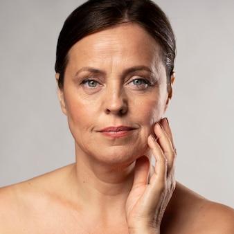 Vista frontal de uma mulher idosa sorridente com maquiagem, posando com a mão no rosto