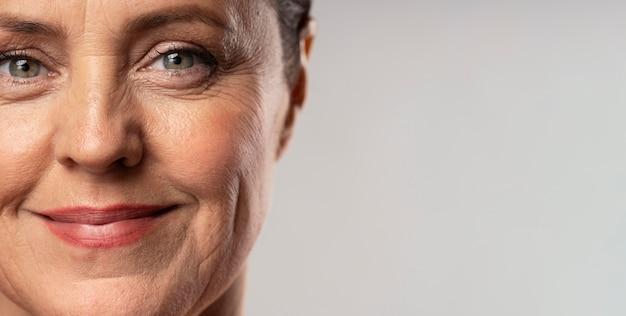 Vista frontal de uma mulher idosa sorridente, posando com maquiagem e espaço de cópia