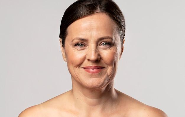 Vista frontal de uma mulher idosa sorridente posando com maquiagem