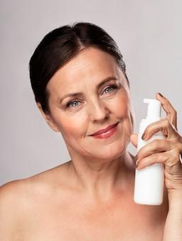 Vista frontal de uma mulher idosa sorridente segurando um frasco de limpador para cuidados com a pele
