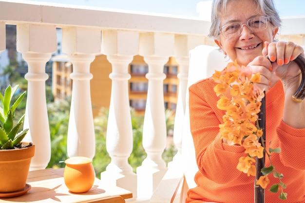 Vista frontal de uma mulher idosa sorridente, sofrendo de osteoartrite, sentada com as mãos apoiadas na bengala