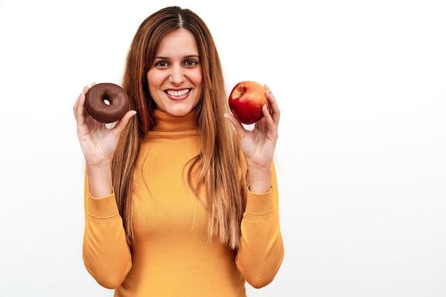 Vista frontal de uma mulher irreconhecível, duvidando do que comer com um donut em uma mão e uma maçã na outra.