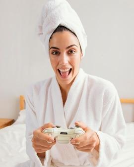 Vista frontal de uma mulher jogando videogame em casa após o banho
