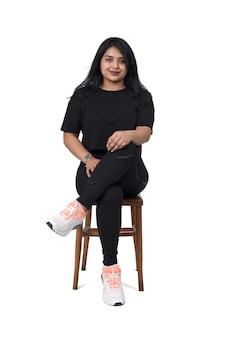Vista frontal de uma mulher latina sentada em uma cadeira com as pernas cruzadas e sorrindo sobre um fundo branco.