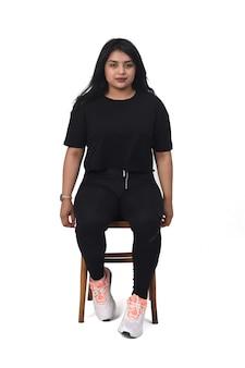 Vista frontal de uma mulher latina sentada em uma cadeira séria sobre fundo branco,