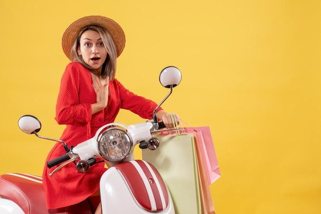 Vista frontal de uma mulher loira com um vestido vermelho em uma motocicleta segurando sacolas de compras e apontando para ela mesma