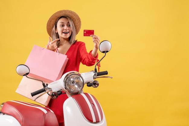 Vista frontal de uma mulher loira feliz com chapéu-panamá na motocicleta segurando sacolas de compras e um cartão