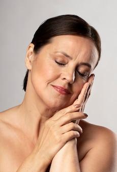 Vista frontal de uma mulher madura posando com maquiagem e olhos fechados