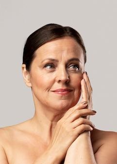 Vista frontal de uma mulher madura posando com maquiagem