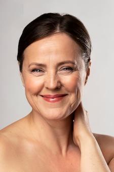 Vista frontal de uma mulher madura sorridente posando com maquiagem