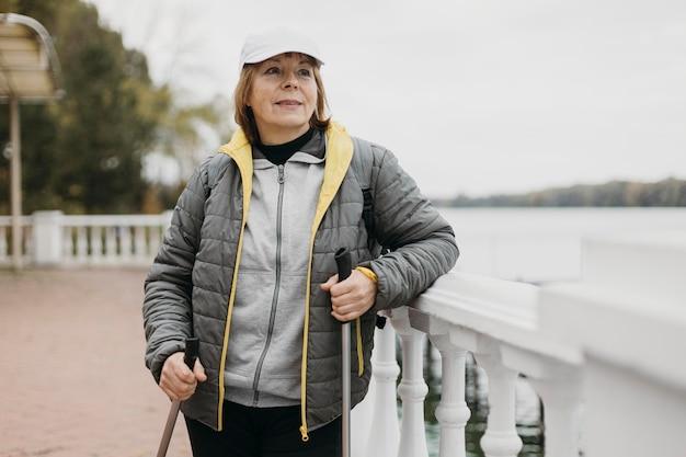 Vista frontal de uma mulher mais velha com bastões de trekking