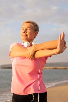 Vista frontal de uma mulher mais velha com fones de ouvido estendendo-se na praia