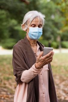 Vista frontal de uma mulher mais velha com máscara médica e smartphone