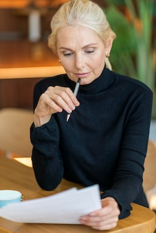 Vista frontal de uma mulher mais velha no trabalho, lendo artigos e pensando